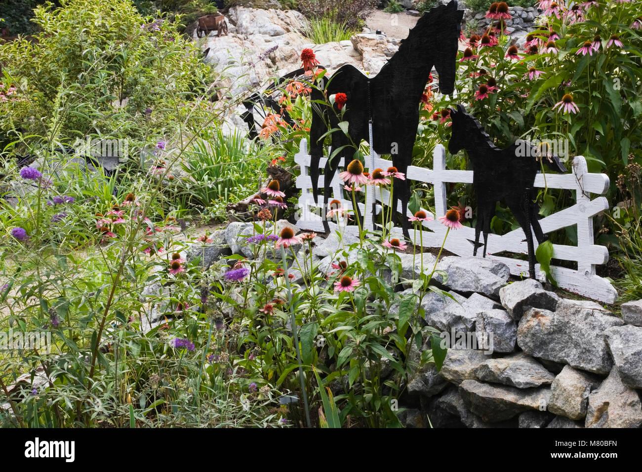 zwei schwarze hölzerne pferd ausschnitte gegen einen weißen zaun in