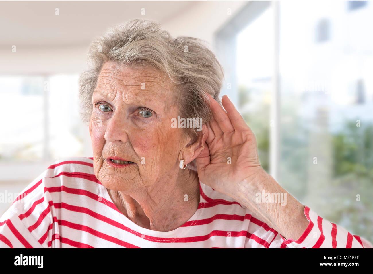 Ältere Dame mit dem Hören Probleme aufgrund der Alterung Hand an ihr Ohr wie Sie kämpft, zu hören, Stockbild