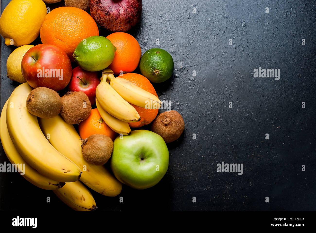 Vielzahl von frischen Zitrusfrüchten auf dunklem Hintergrund aus Schichten von Kiwi, Bananen, aplle und orange, Stockbild
