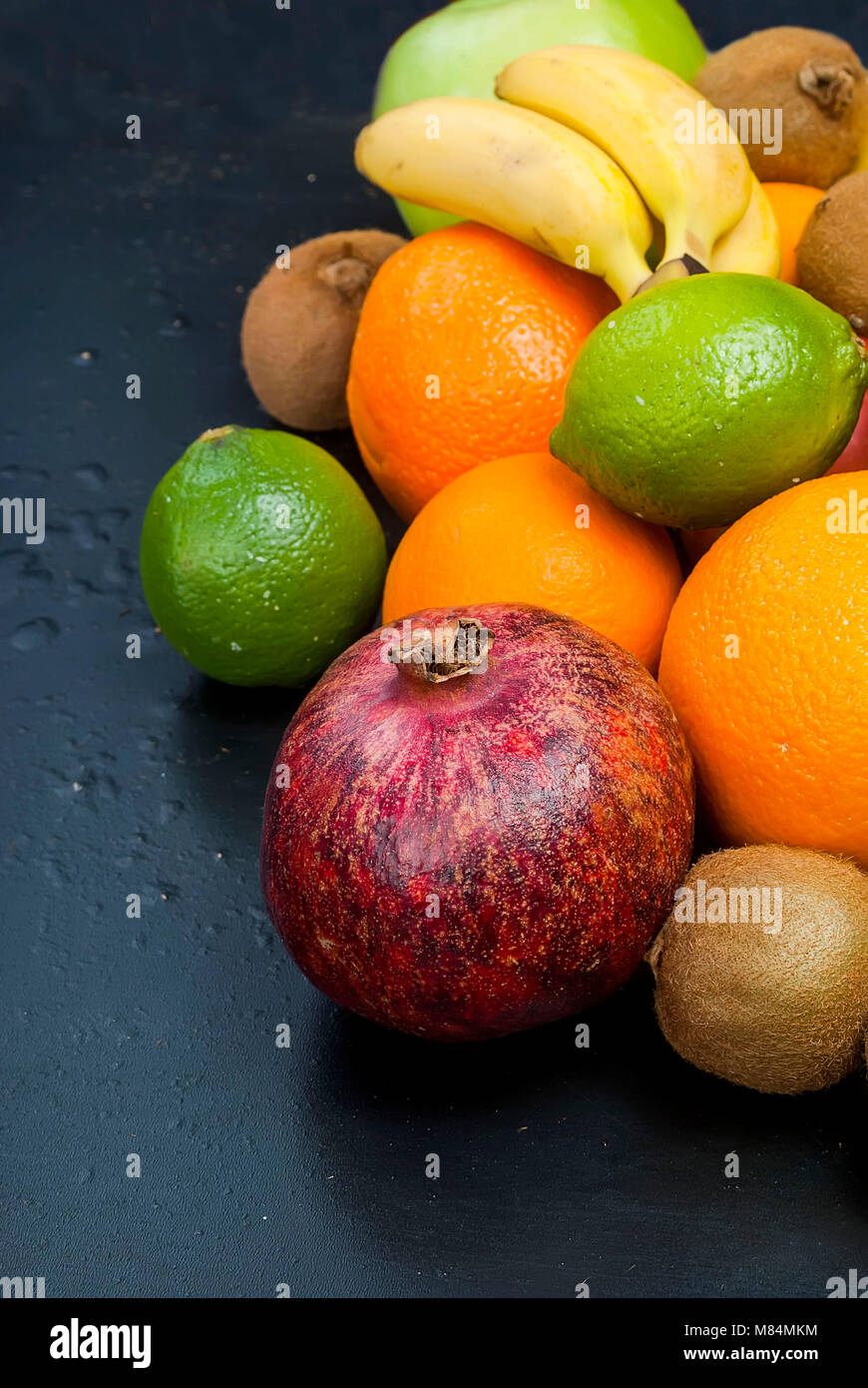 Auswahl an frischem Obst auf dunklem Hintergrund aus Schichten von Kiwi, Bananen, aplle und orange, kopieren Raum Stockbild
