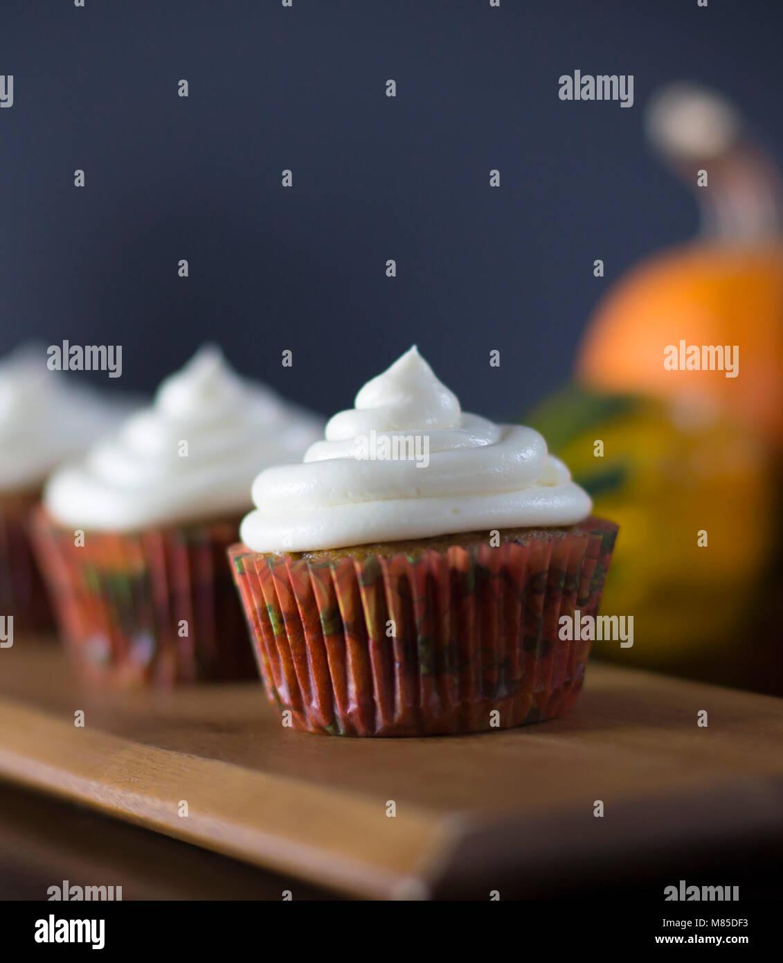 Köstliche Pumpkin Spice Cupcakes mit Cream Cheese Frosting mit Kürbissen im Hintergrund Stockbild