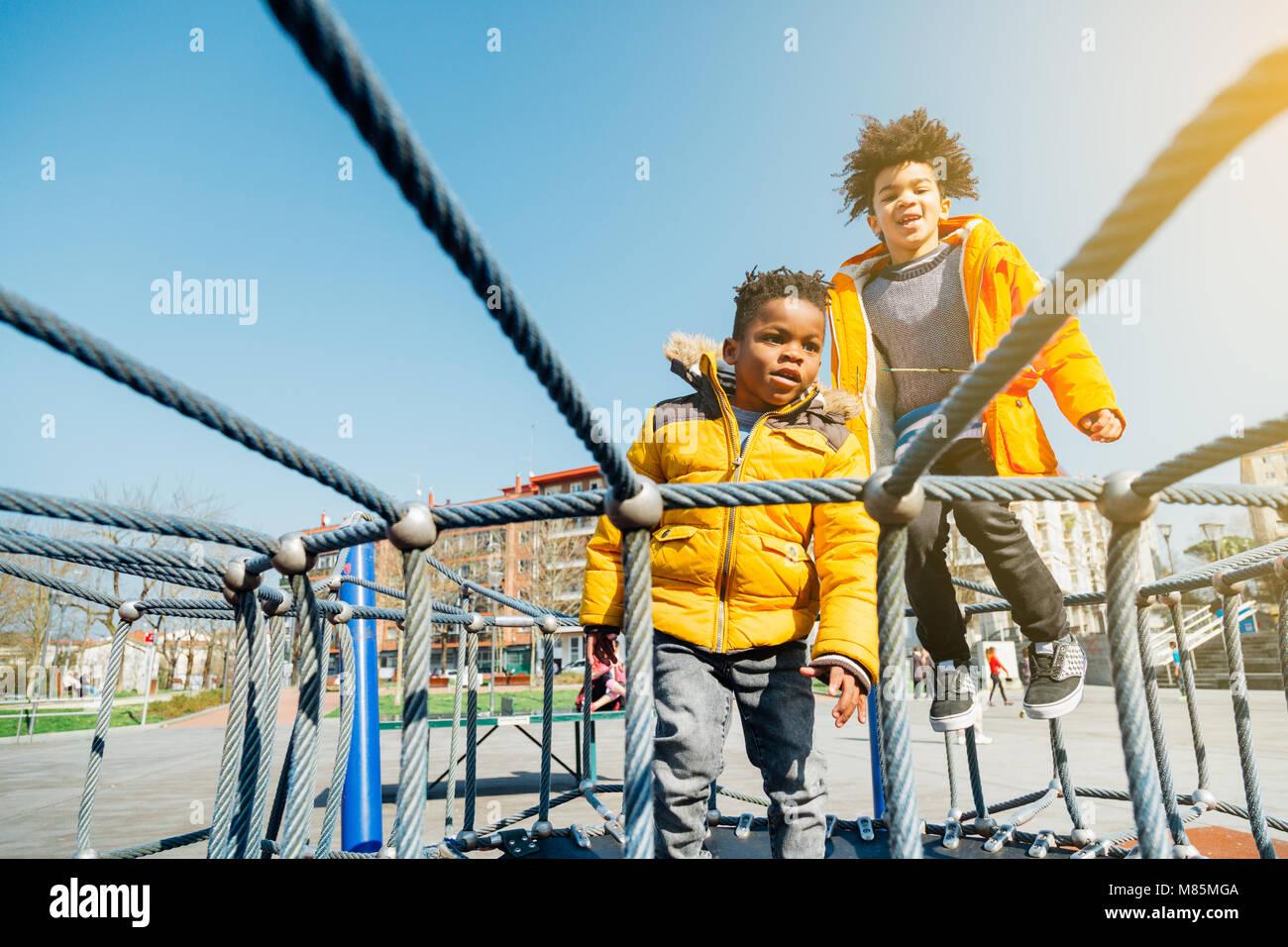 Zwei Kinder mit gelben Mänteln springen auf elastischen Bett in einem Spielplatz an einem sonnigen Tag Stockbild