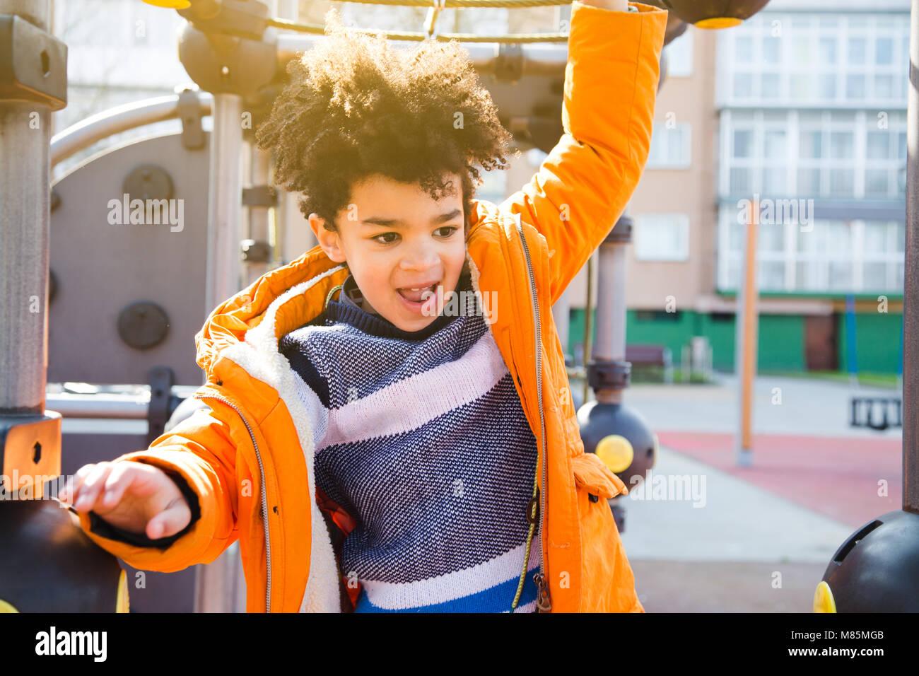 Glückliches Kind in orange Mantel Klettern auf dem Spielplatz an einem sonnigen Tag Stockbild