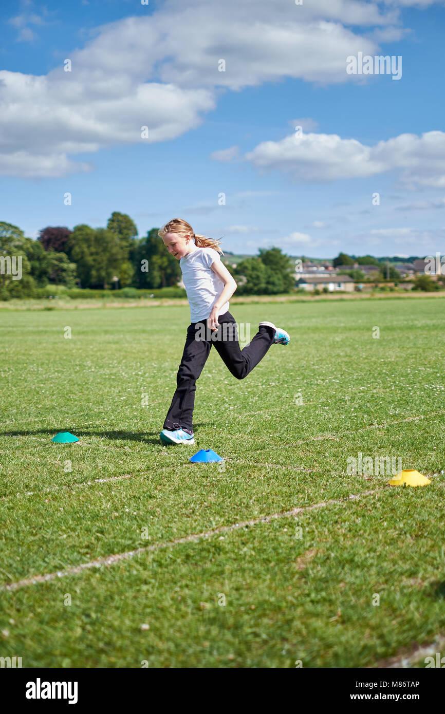 Ein junges Mädchen über die Ziellinie fährt in einem laufenden Fall auf einer Grasbahn im Sommer Stockfoto