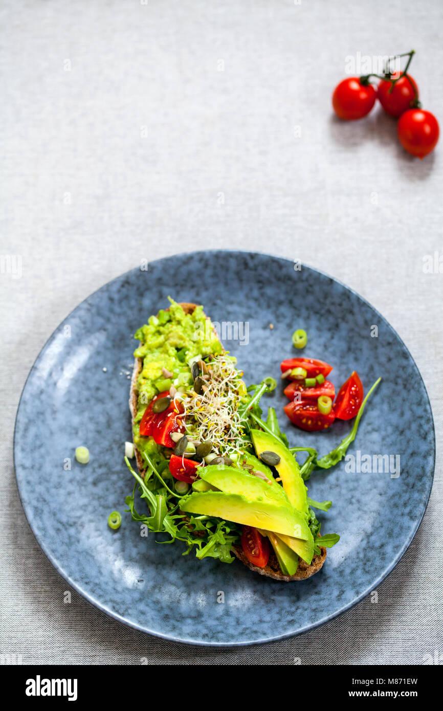 Roggen Toast mit Avocado, Tomaten und Alfalfa Sprossen Stockbild