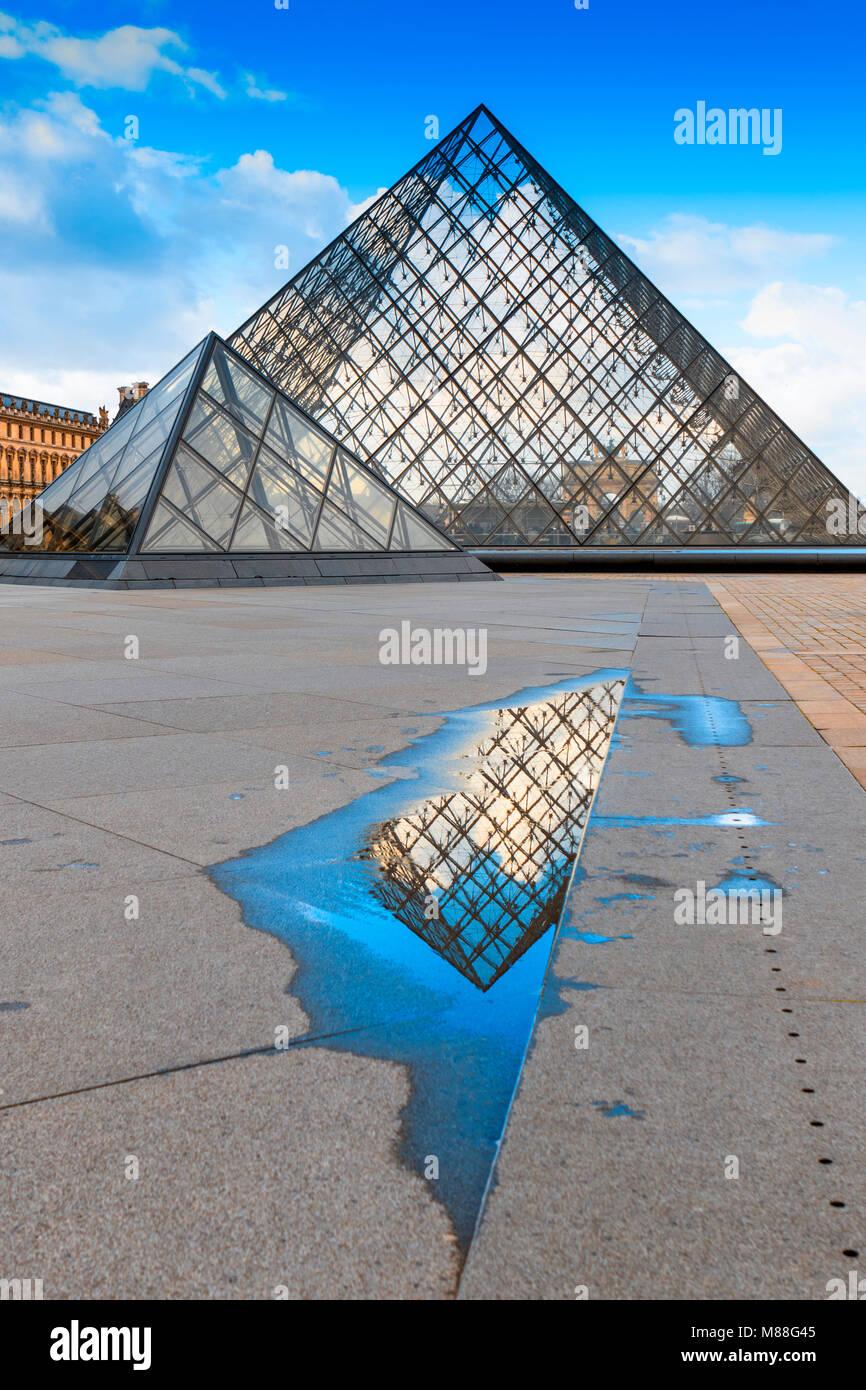 Glas Pyramiden des Louvre in Paris, mit abstrakten Reflexion im Wasser aus der Pfütze von der Regen während Stockbild