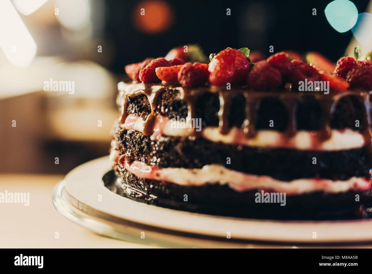 Schokoladenkuchen mit Sahne und Früchten Stockbild