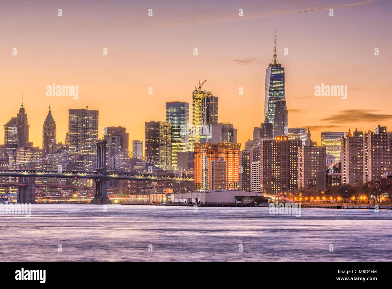 New York City, USA Skyline auf den East River und die Brooklyn Bridge in der Abenddämmerung. Stockbild