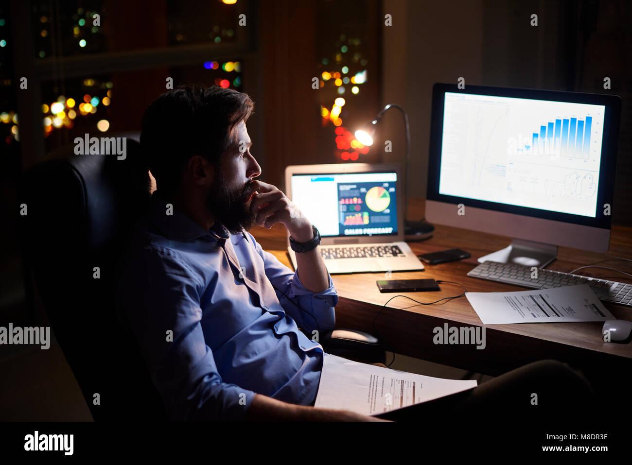 Junge Unternehmer starrte auf Computer im Büro Schreibtisch bei Nacht Stockbild