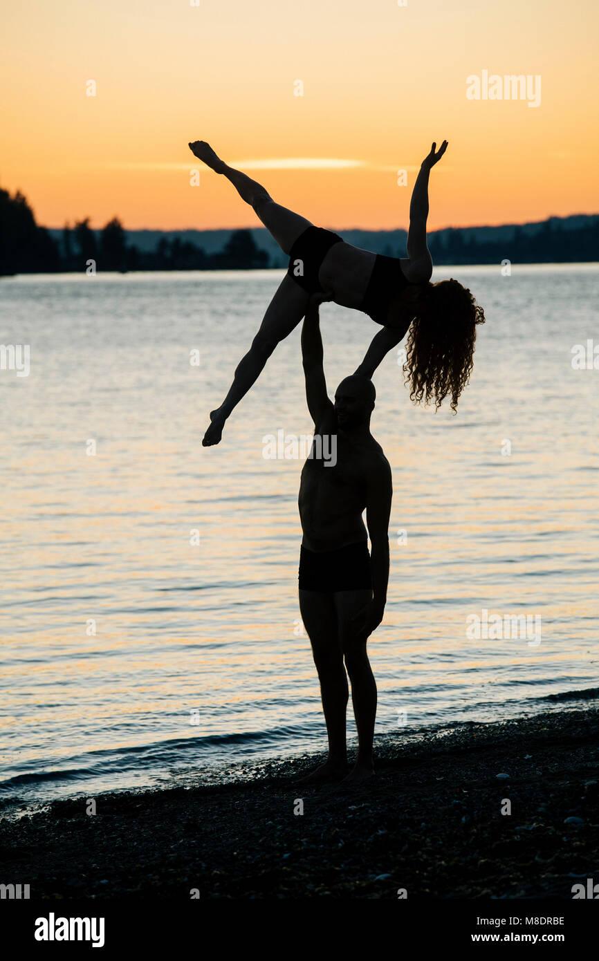 Paar Üben Yoga am Strand bei Sonnenuntergang Stockbild