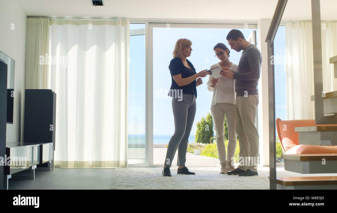 Professionelle Immobilien Agent zeigt ein stilvolles, modernes Haus mit einem schönen jungen Paar, das auf dem Markt Stockfoto