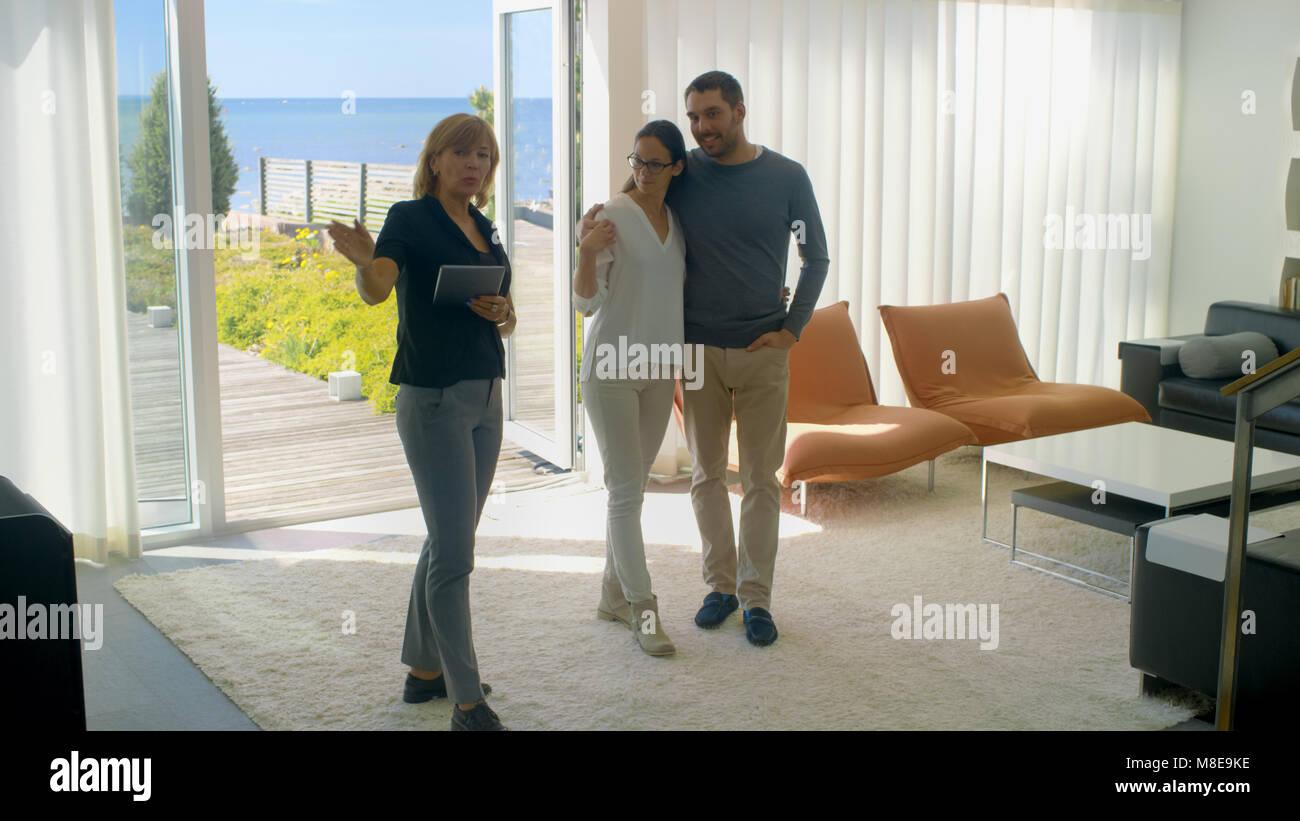 Professionelle Immobilien Agent zeigt ein stilvolles, modernes Haus mit einem schönen jungen Paar, das auf Stockbild