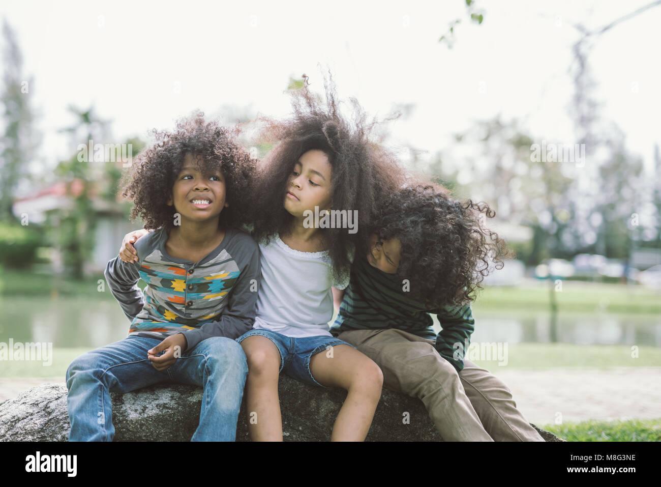 Kinder Freundschaft miteinander Lächeln Glück Konzept. Cute afrikanische amerikanische kleine Jungen und Mädchen umarmen sich in park Stockfoto