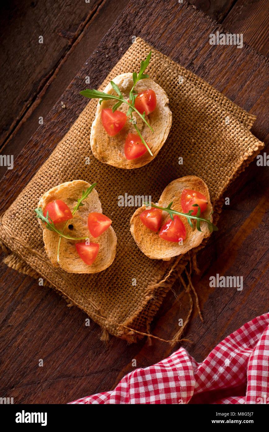 Drei Bruschetta mit Tomaten und Rucola Stockbild