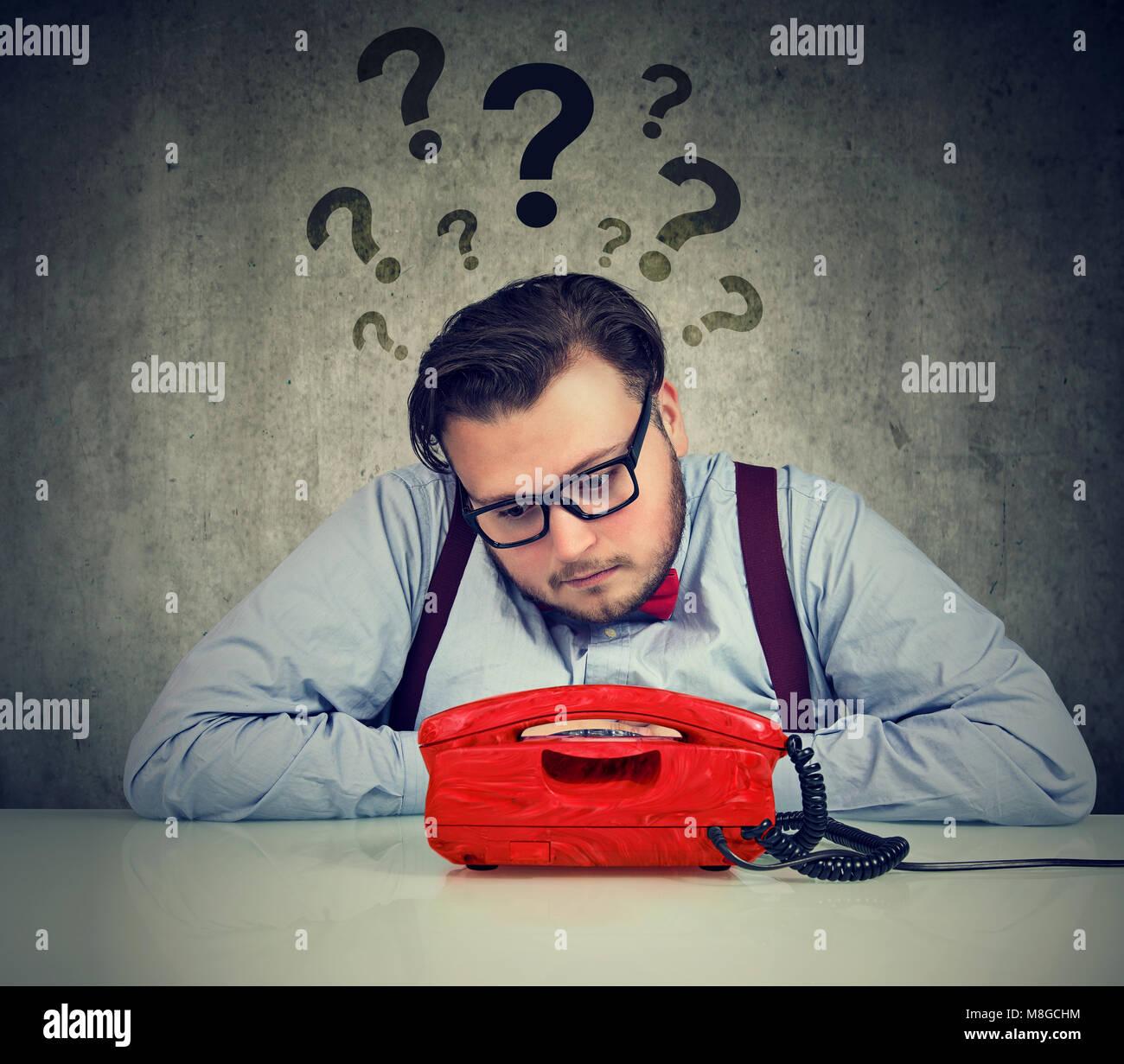 Mann traurig mit zu vielen Fragen, die auf einen Anruf warten Stockbild