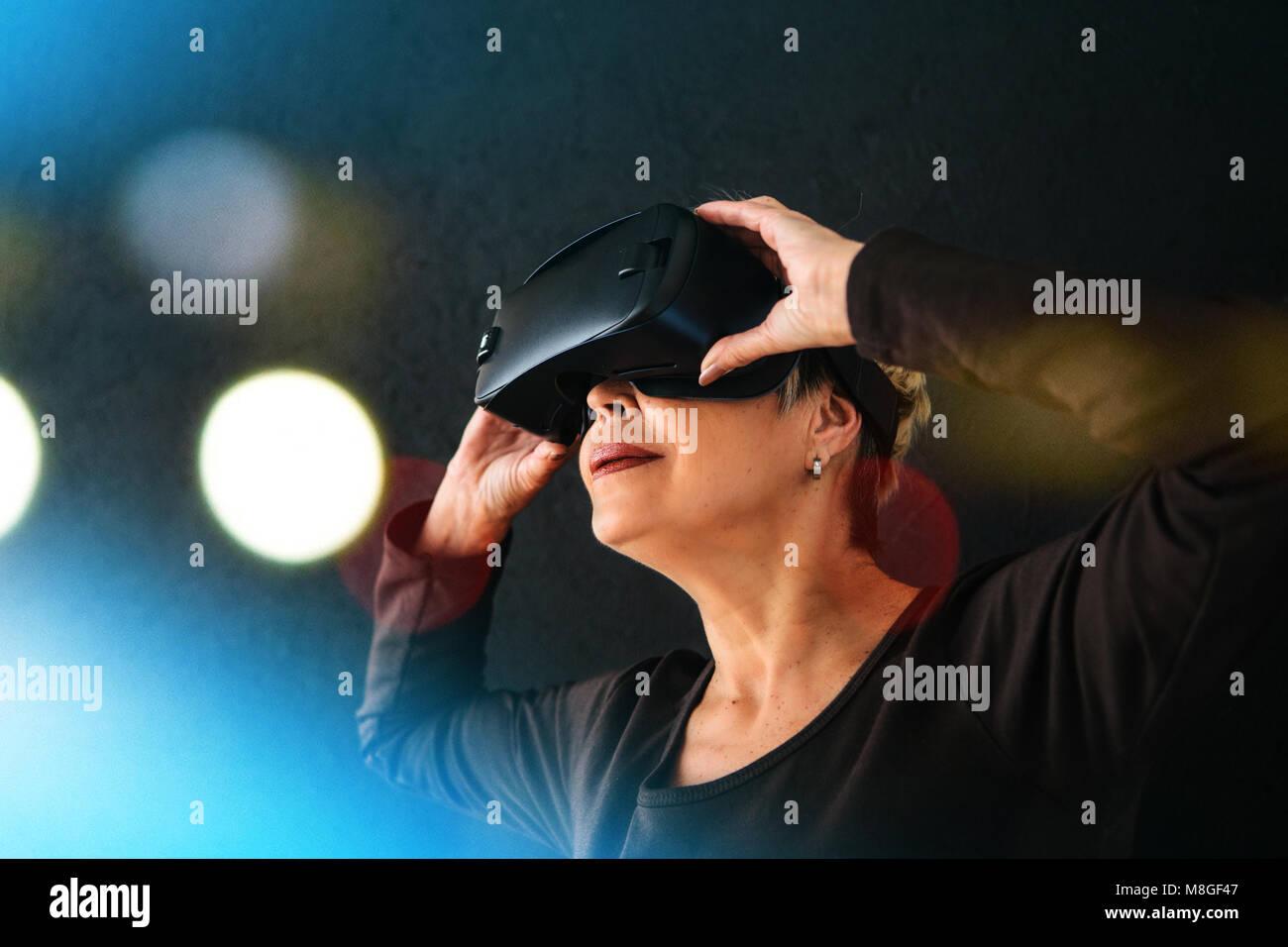 Eine ältere Frau in der virtuellen Realität Gläser. Eine ältere Person mit moderner Technologie. Stockbild