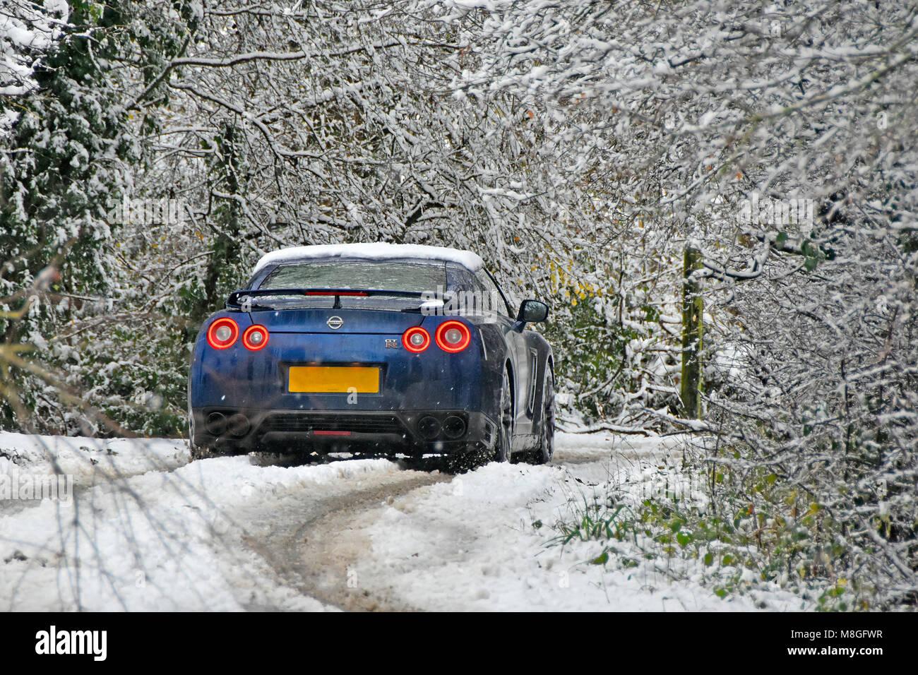 Verschneiter baum landschaft Szene Auto in der schmalen Straße hinunter Feldweg im Winter Schnee fallen, ländlichen Stockbild