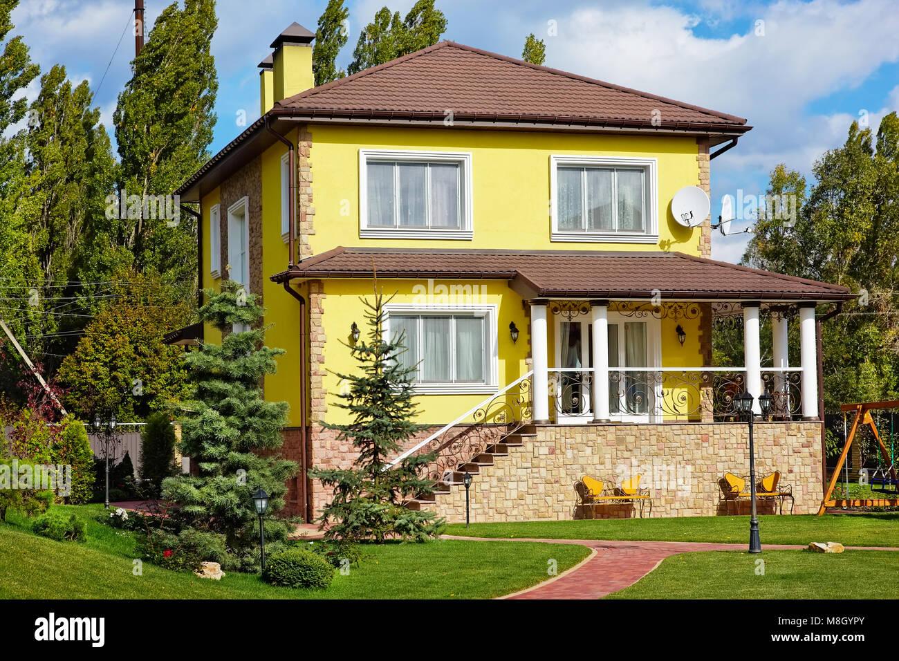 Von außen schönes Haus mit grünem Garten und Kinderspielplatz ...