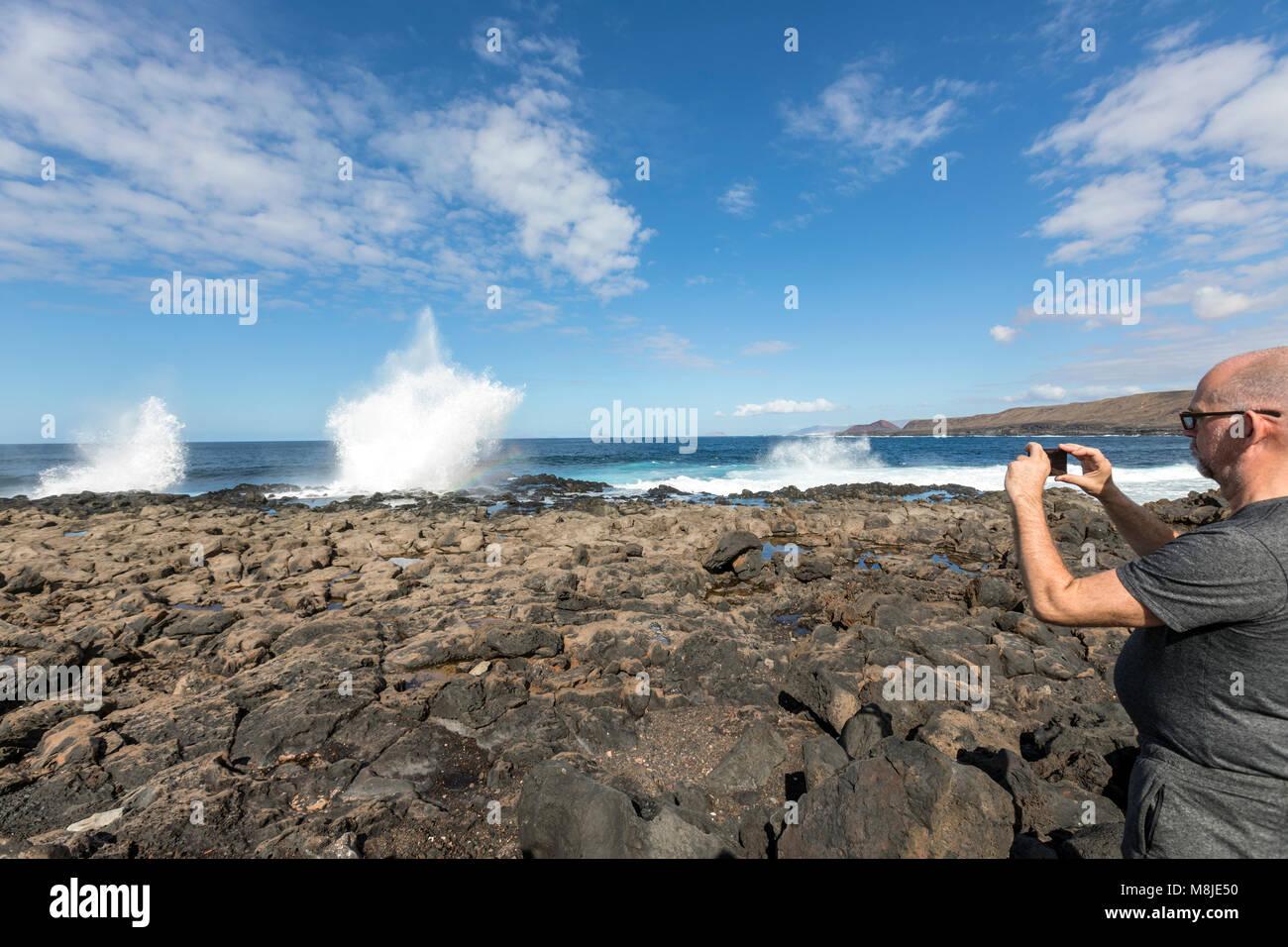 Tourist, der ein Bild von einem tapferen Meer in Tenesar, Lanzarote, Kanarische Inseln, Spanien Stockbild