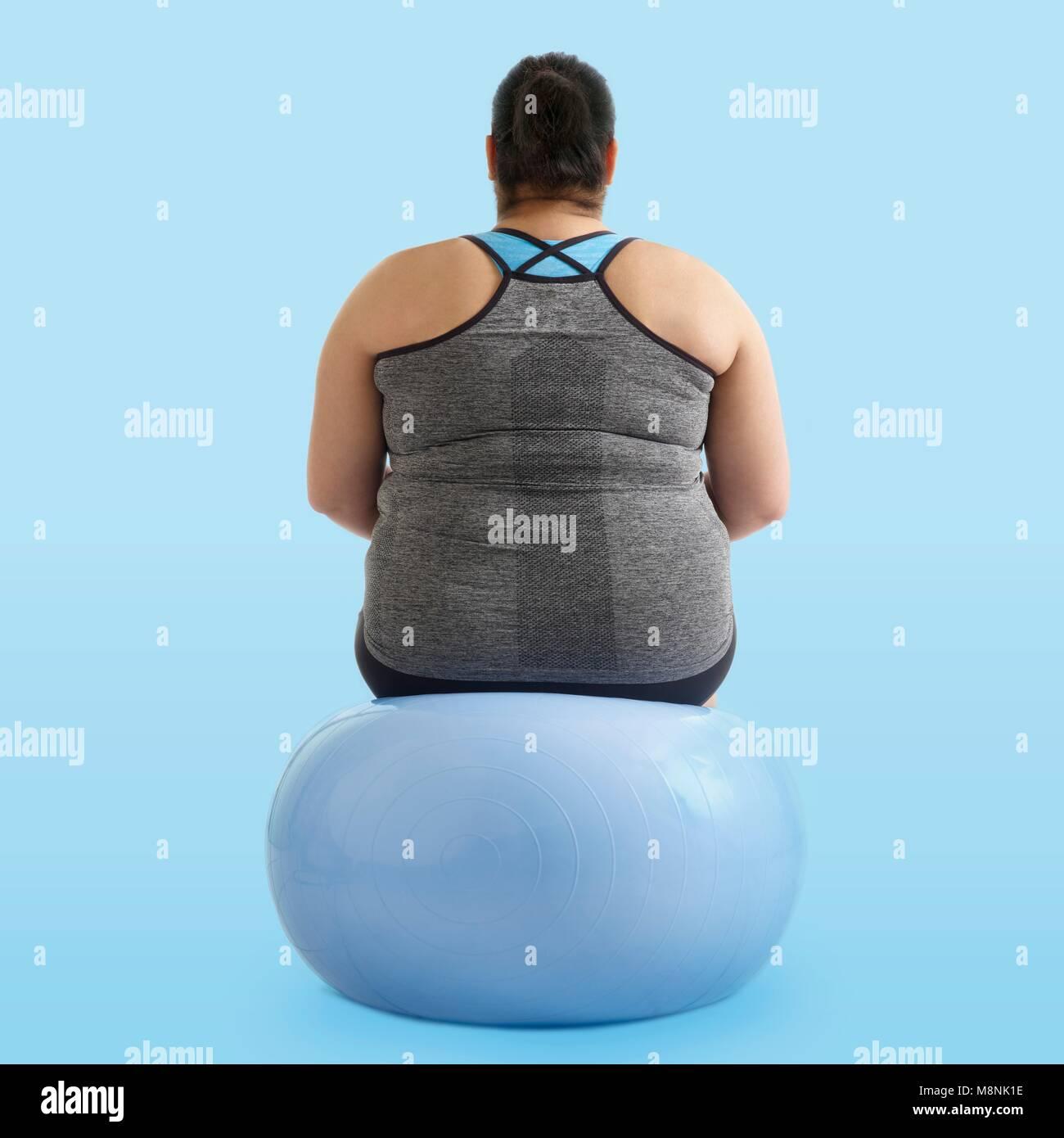 Übergewichtige Frau sitzt auf einer übung Kugel, Ansicht von hinten. Stockbild