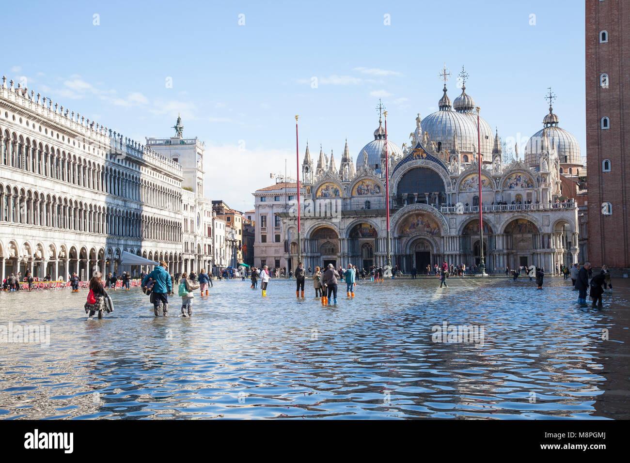 Touristen zu Fuß durch die Acqua Alta High Tide mit Koffer, Markusplatz, Piazza San Marco, Venedig, Venetien, Stockbild