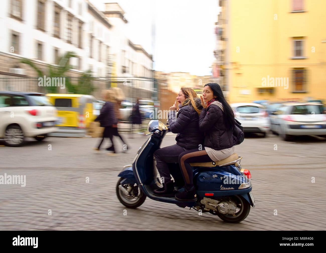 Zwei Frauen ohne Fahrrad Helme auf einen Roller über Concezio Muzt, Centro Storica, Napoli Stockbild