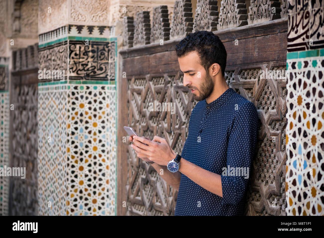 Junge muslimische Mann über sein Mobiltelefon in Freizeitkleidung neben der Wand mit traditionellen marokkanischen Stockbild