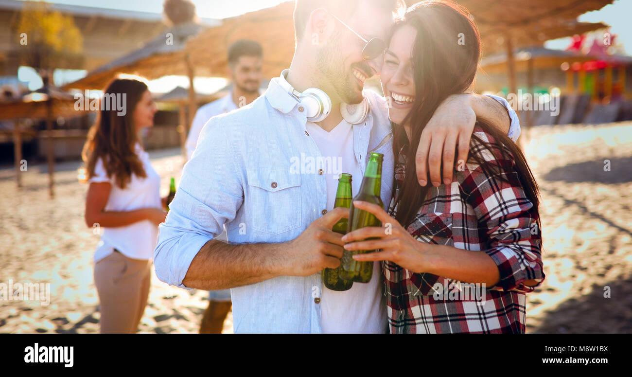 Glückliches junges Paar Bier trinken und Spaß am Strand Stockbild