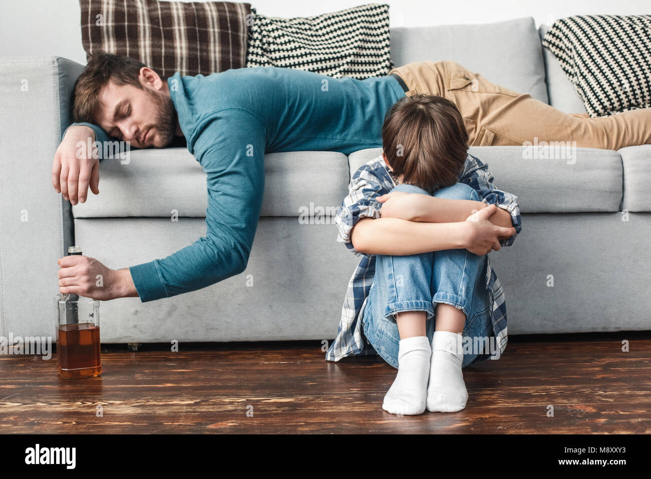 junge und vater alkoholiker zu hause sohn sitzen weinen einsam w hrend papa schlafen betrunken. Black Bedroom Furniture Sets. Home Design Ideas