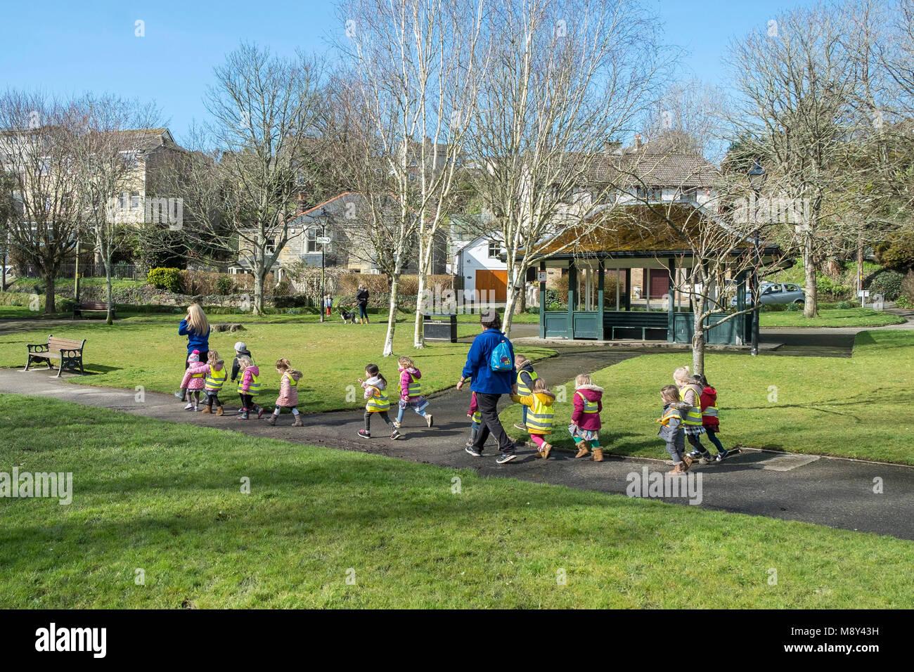 Kinder aus einem Kindergarten und ihre Lehrer gehen obwohl Trenance Gärten in Newquay Cornwall. Stockbild