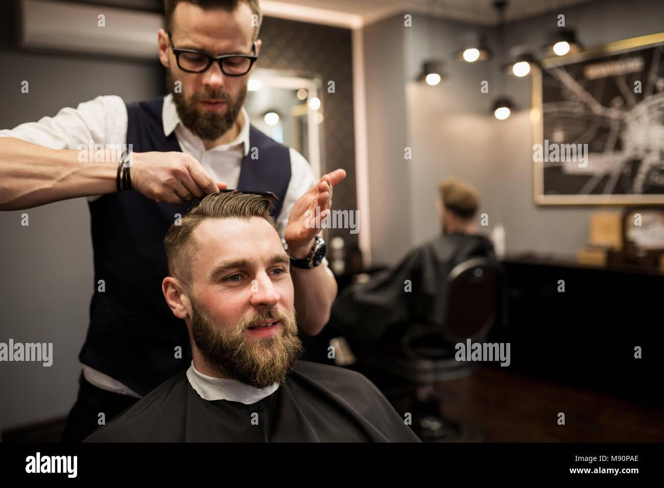 Portrait von froher Kunde in die Haare schneiden, die im Salon Stockbild