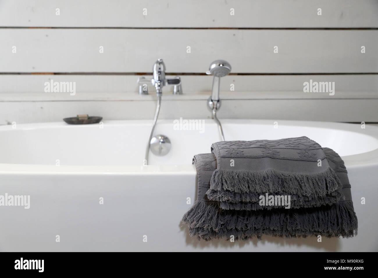 Moderne Keramikbadewanne mit Handtüchern. Stockbild