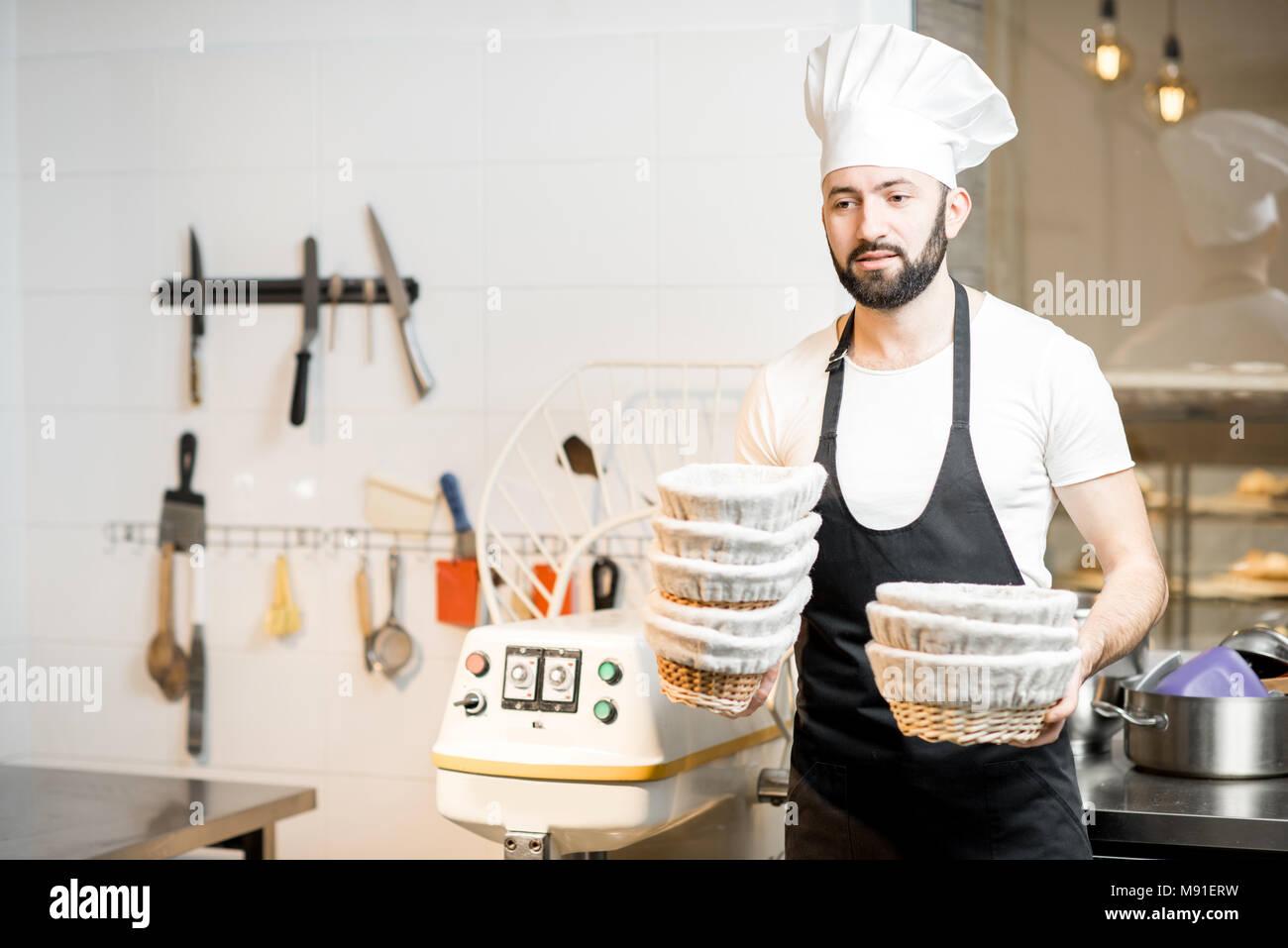 Bäcker mit backformen in der Bäckerei Stockbild
