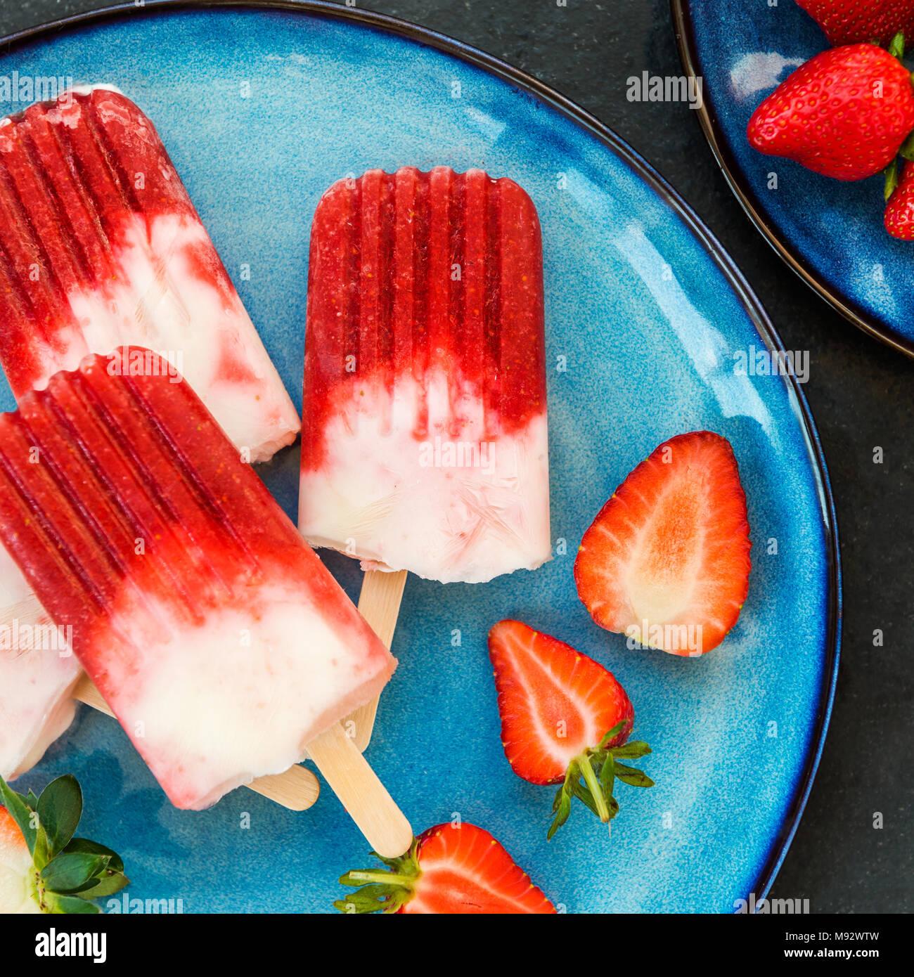 Hausgemachte Vegan Erdbeere Popsicle mit Erdbeersaft und Kokosmilch auf dunklem Marmor Hintergrund. Sommer essen Konzept. Ansicht von oben. Stockbild