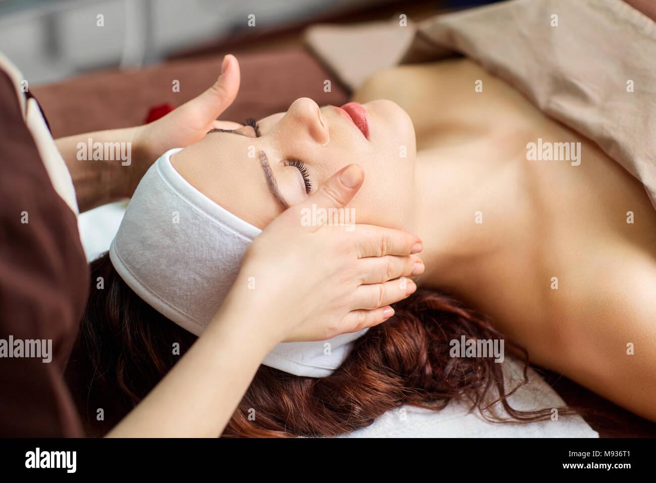 Schöne Frau an eine Gesichtsmassage in einem Spa Salon Stockbild