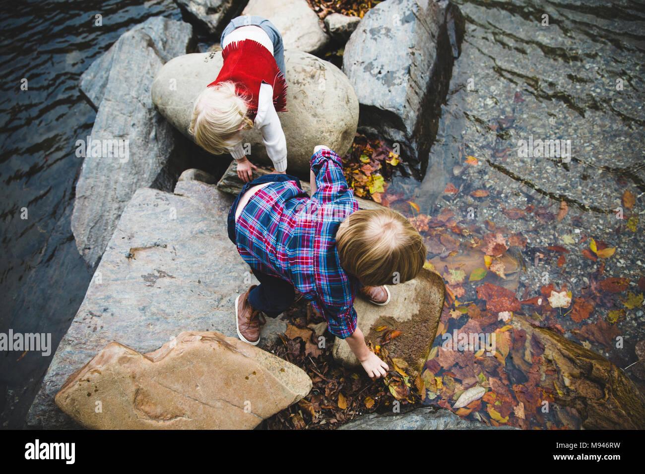 Kinder spielen auf den Felsen am Fluss Stockbild
