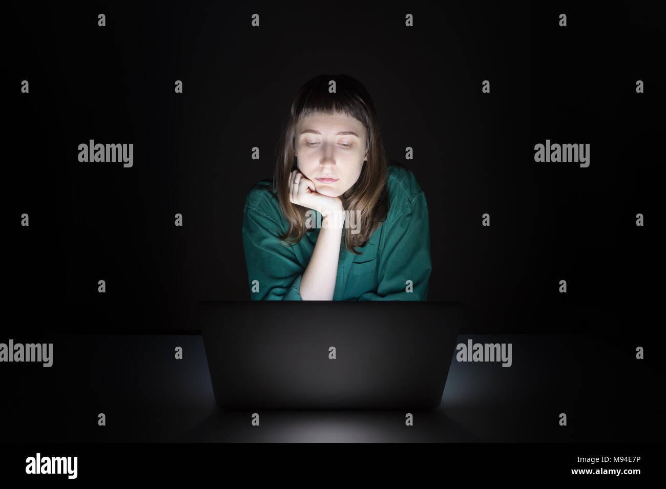 Frau am Laptop zuhause spät in den Abend. Porträt der jungen Studentin oder Arbeiter sitzen vor dem Bildschirm in der Nacht und lesen Stockbild