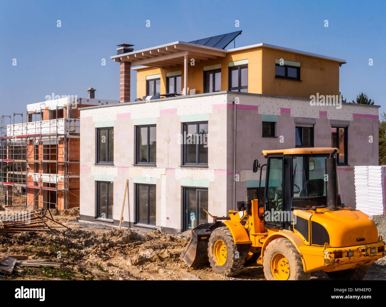 Ein neues Gebäude neben einem Shell in einem Baustellenbereich mit einem Radlader im Vordergrund.Stockfoto