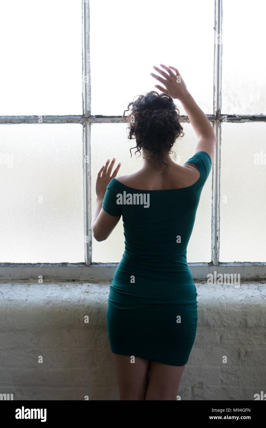 Rückansicht eines einsamen Frau, die durch die Fenster mit den Händen berühren das Glas Stockbild