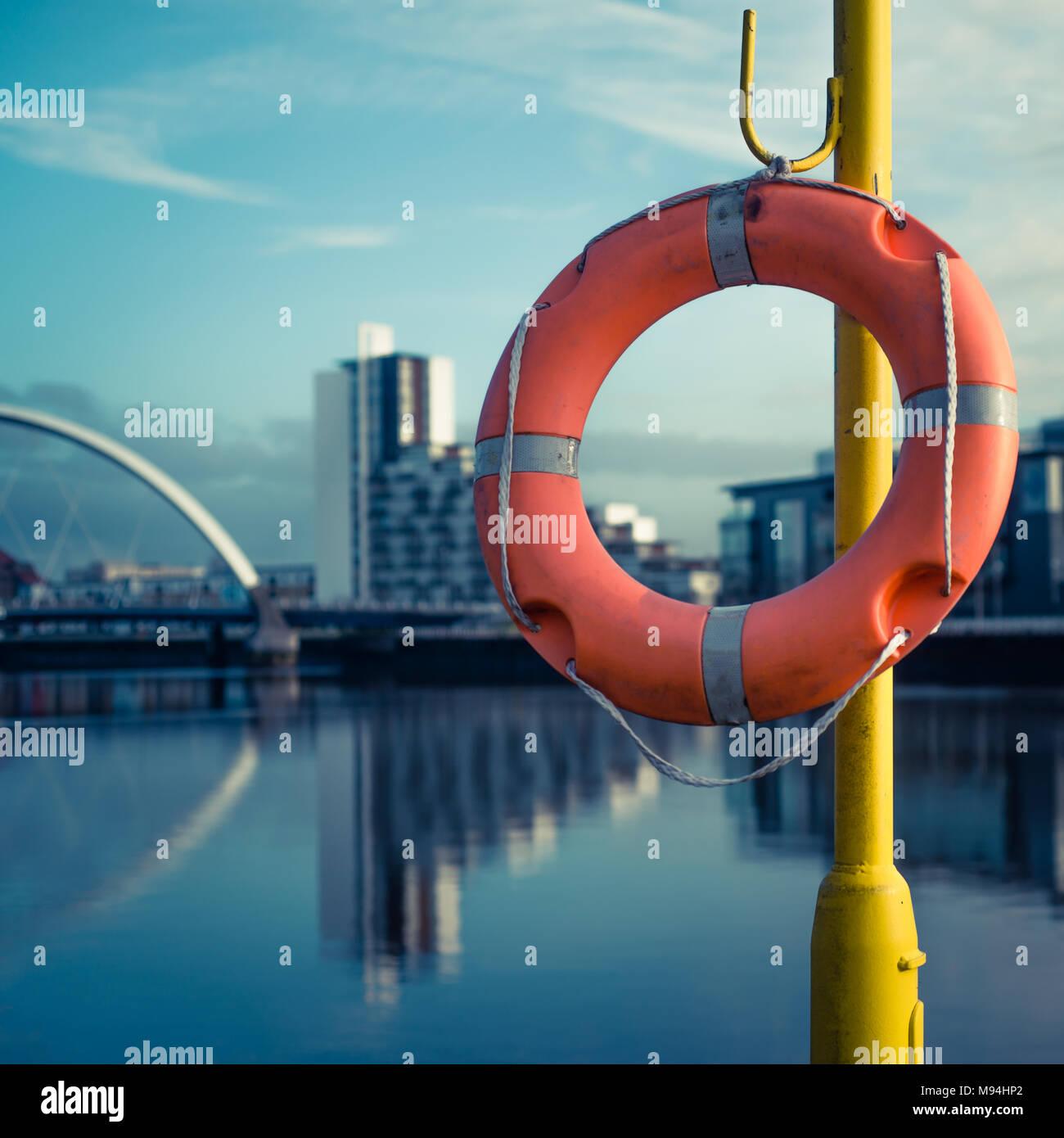 Orange Leben Boje mit Fluss Clyde und Arc Bridge im Hintergrund Stockbild