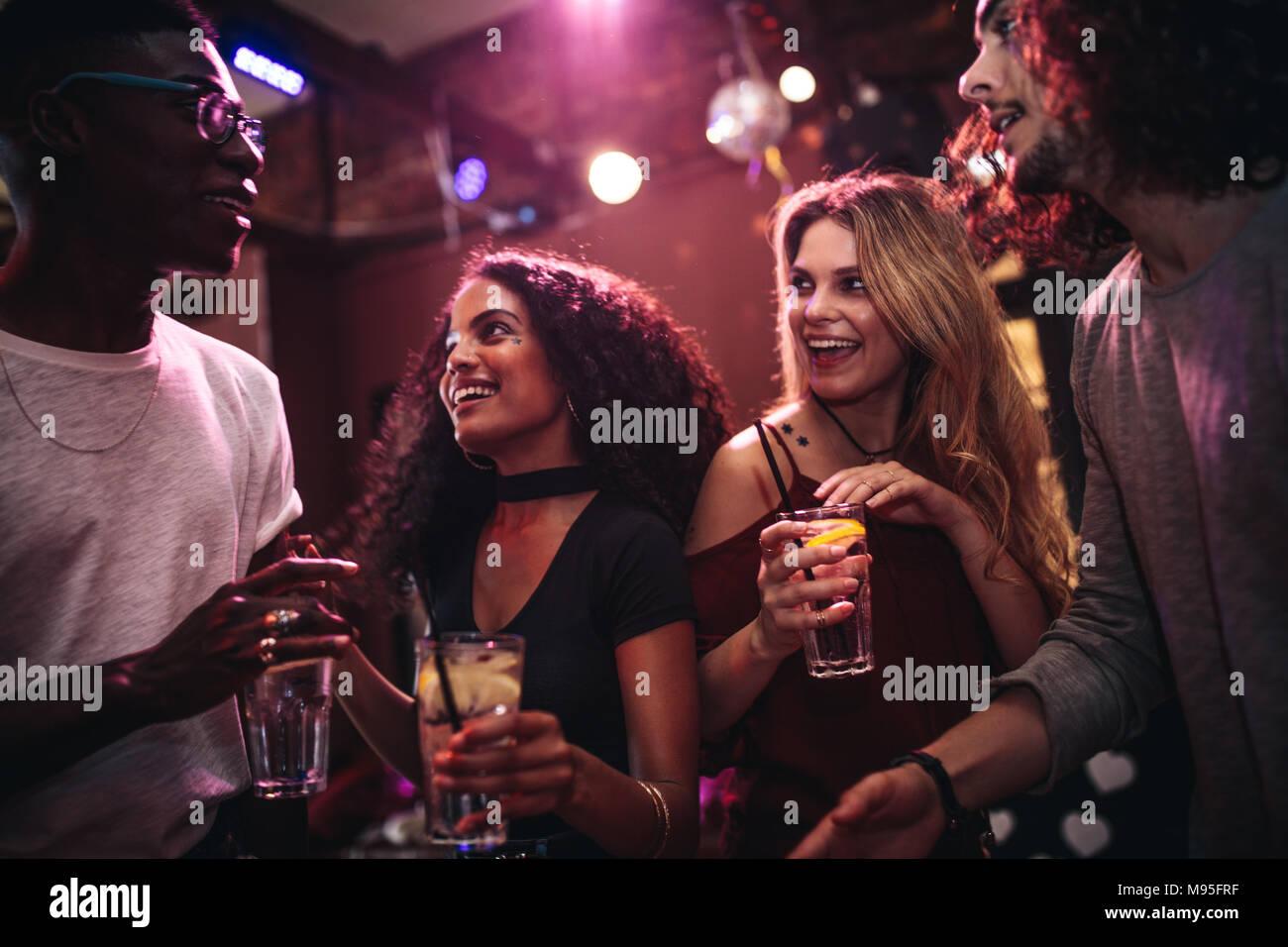 Vielfältige Gruppe von jungen Menschen mit Getränken in einem Club. Glückliche Männer und Frauen genießen nightout an der Bar. Stockbild