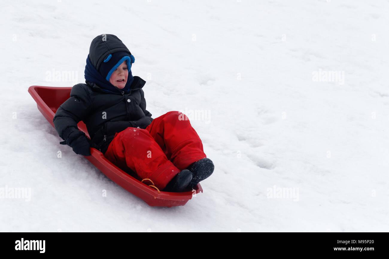 Ein kleiner Junge (5 Jahre) Suchen Sie erschrocken, als er Schlitten einen steilen vereisten Steigung Stockbild