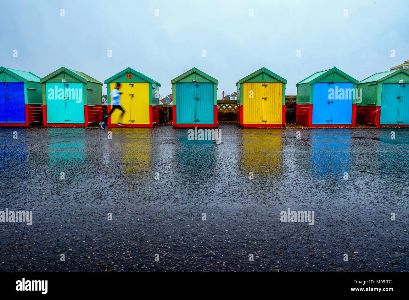 Brighton Seafront sieben Badekabinen, fünf mit blauen und grünen Türen und zwei mit gelben Türen die Strandhütten in einer Linie auf einer konkreten Promenade sind die Stockfoto