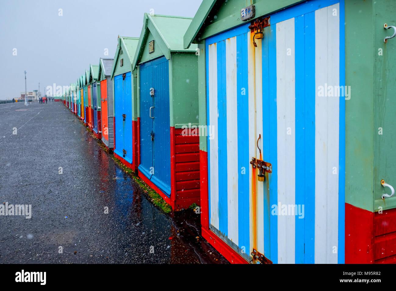 Brighton Seafront vierzig Badekabinen, die Hütten haben mehrfarbige Türen in einer geraden Linie auf eine konkrete Promenade der Himmel grau ist der nächstgelegene Strand h Stockbild