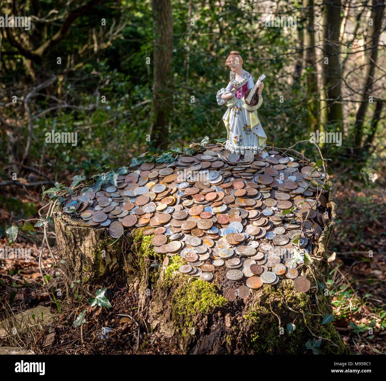 Keramik Fee und Münzen links so viel Glück Token auf einem Baumstumpf in der Nähe der Kanzel des Teufels über das Wye Valley in Monmouthshire UK Stockbild