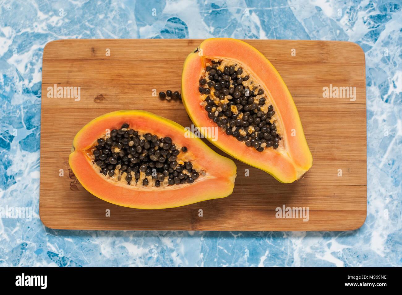 Die Papaya liegt auf einer hölzernen Hintergrund. Die beiden Hälften des exotischen Früchten. Stockbild