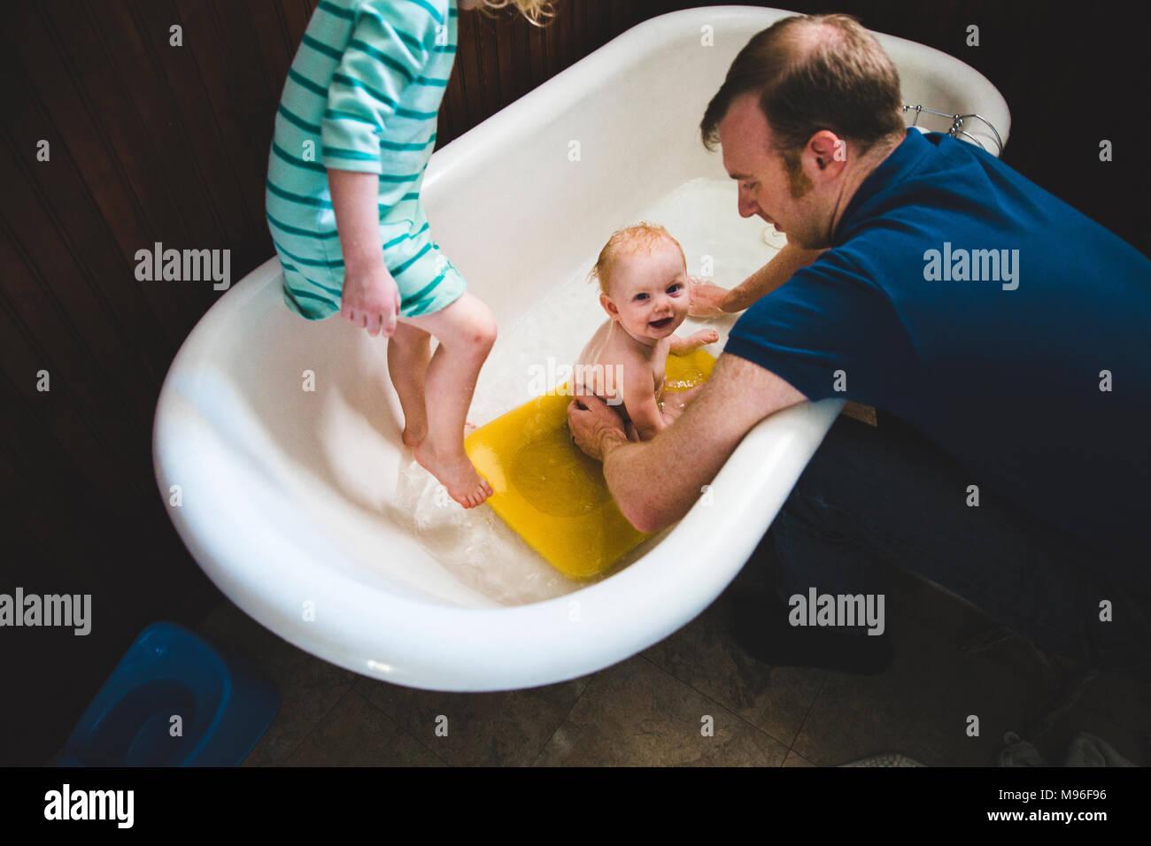 Waschen Vater Baby in Wanne mit anderen Mädchen Stockbild