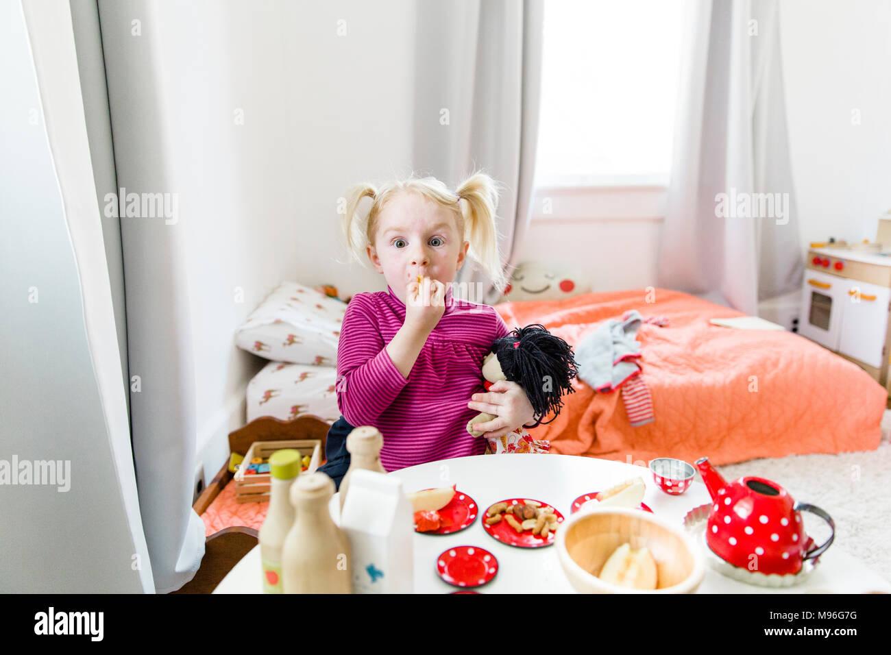 Mädchen mit Puppe sitzend am Tisch essen Stockbild