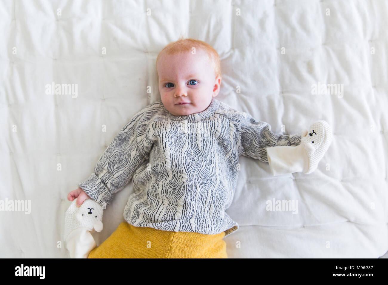 Baby liegend auf Bett mit Handschuhe Stockbild