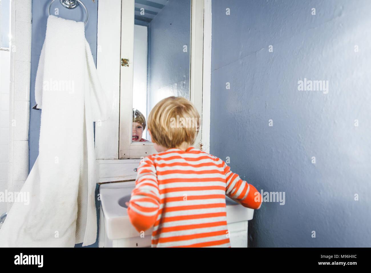 Junge Kontrolle seine Zähne im Spiegel Stockbild